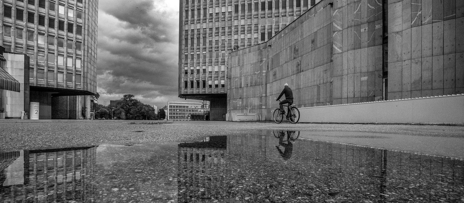 Man on bike and his reflection in front of buildings at the republic square, Ljubljana. Photo by Iztok Boncina.